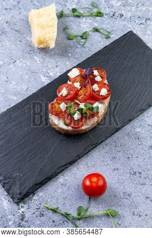 Bruschetta With Mini Tomatoes And Cheese On A Gray Background