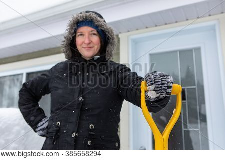 A Woman Putting Her Hand On Shovel Grip. Out Of Focus In The Background A Portrait Of Satisfied And