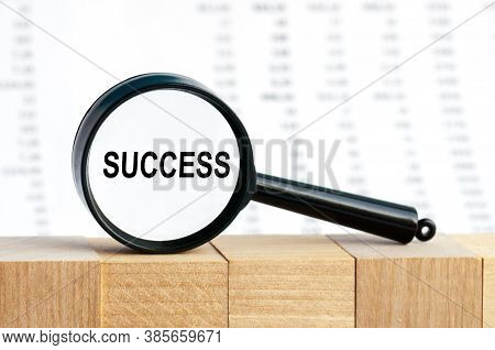 Looking Through A Magnifying Glass At The Word Success, A Business Concept. Magnifying Glass On The