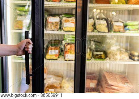 Selective Focus View Of A Hand Holding The Handle Of A Refrigerator To Open It In The Supermarket Wi