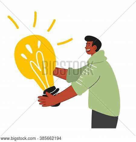 A Young Scientist Holds A Huge Glowing Light Bulb In His Hands, As A Symbol Of An Idea. Startup And