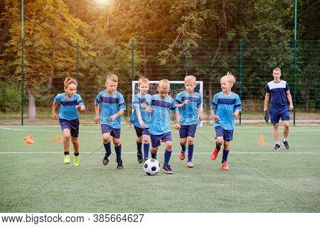 Children Running And Kicking Soccer Ball On Children Football Training Session