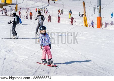 Young Happy Skier Girl Learning How To Ski On The Green Ski Zone. Young Skier Having Fun On Ski Slop