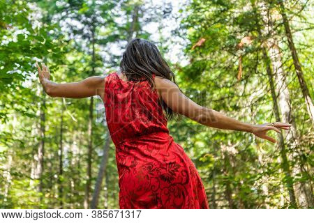 View From Behind Of A Slender Young Woman In A Red Dress Dancing A Ritual Energetic Dance In The Mid