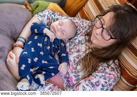 View From Above Of A Mother Holding Her Young Infant Son In Monkey Patterned Romper, Both Snooze In