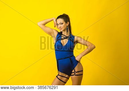Sexy Female Pole Dancer Wearing Blue Bodysuit And High Heels On Yellow