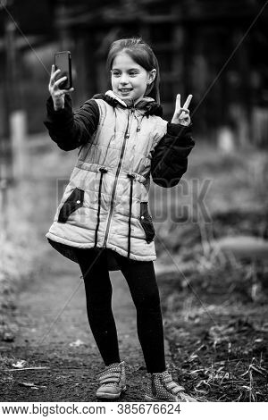 Little girl makes selfie on the phone outdoor. Black and white photography.