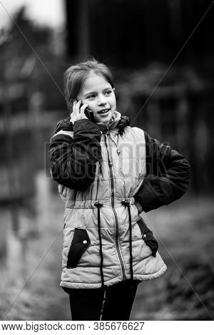 Little girl talking on mobile standing in the street. Black and white photography.