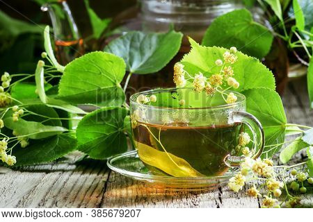Traditional Russian Linden Tea, Flowers And Linden Branches, A Vintage Wooden Background, Selective