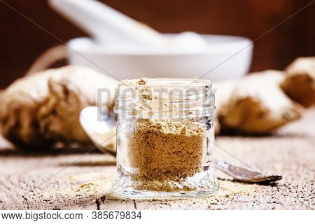 Ground Ginger In A Glass Jar And Fresh Ginger Root, Vintage Wooden Background, Selective Focus