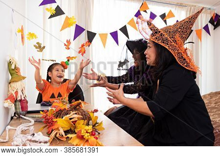 A Girl Dressed In A Pumpkin Costume Throwing Dry Leaves Into The Air While Two Women Dressed In Witc