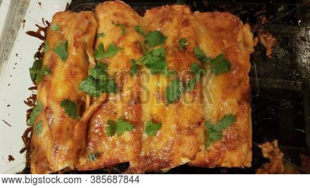 Cheesy Enchiladas With Cilantro In Glass Container On Stove