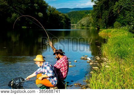 Two Men Fishing On River. Man Catching Fish. Fly Fishing Adventures. Mature Man Fly Fishing. Fishman