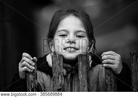 Portrait of little girl behind a wooden fence in the village. Black and white photo.