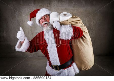 Smiling Santa Claus holding a sack full of toilet paper and giving the thumbs up sign during a pandemic