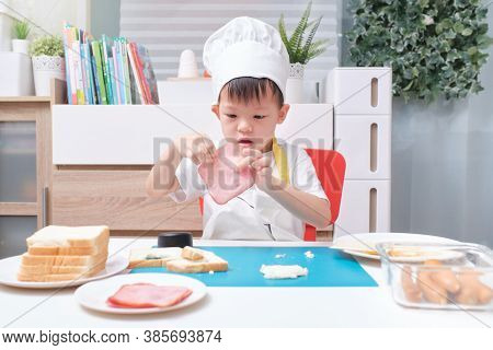 Cute Asian Boy Wearing Chef Hat And Apron Having Fun Preparing Sandwiches, Little Kid Holding Ham Wh