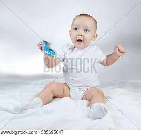 Photo Of A Ten-month-old Baby Boy Holding Blue Rattle