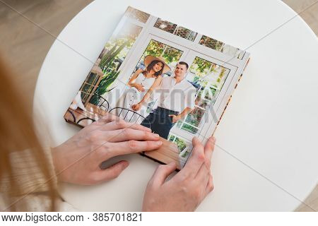 A Woman Hold In Hands A Photo Book From A Family Pregnancy Photo Shoot. Beautiful And Convenient Sto