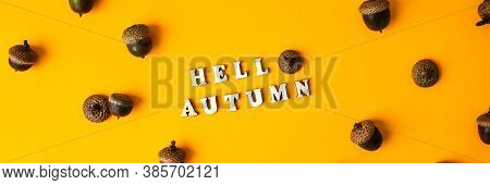 Inscription Hello Autumn Text Pattern With Acorns On The Yellow Background. Autumn Concept. Pattern