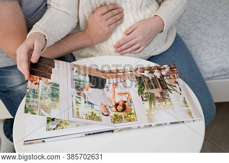 Close Up. A Couple Waiting For The Baby Flips Through A Photobook From A Family Pregnancy Photo Shoo
