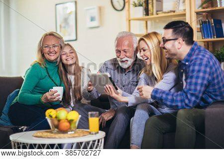 Multi Generation Family Relaxing At Home Together Using Digital Tablet