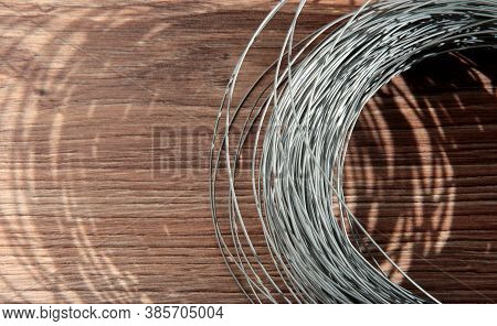 Wire On A Wooden Background. Shadow From A Coil Of Steel Wire.