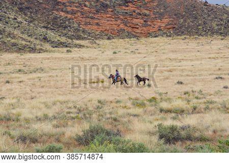 Utah Usa - September 23 2015; Cowboy And Pony Galloping Through Utah Landscape Dry Grass Below Hill.