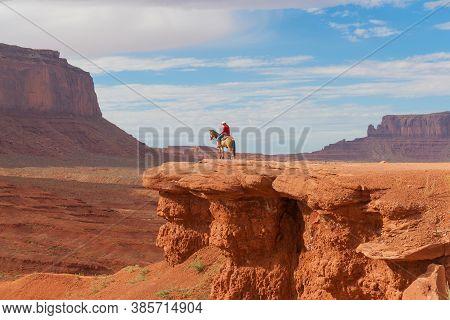 Utah Usa - September 23 2015; Cowboy On Horseback On Red Rock Ledge In Monument Valley Among Imposin