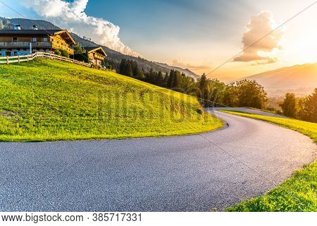 Romantic Sunset In The Mountains. Alpine Rural Curvy Road, Green Meadows And High Peaks Of Austrian