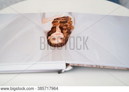 Wedding Photo Book. Flipping Through A Wedding Photobook With Thick Pages On A White Table. Convenie