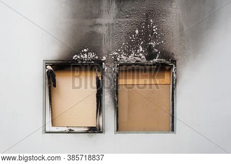 House Or Home Fire - Boarded Up Windows And Burned Facade Blackened By Soot Of Modern Apartment Buil