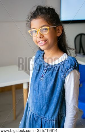 Portrait Of Mixed-race Girl In Eyeglasses. Cute Confident Child Posing In Classroom After Lesson, Sm