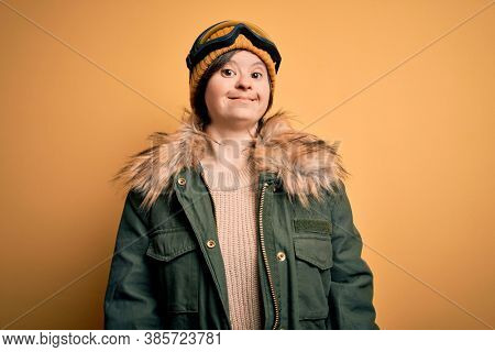 Young down syndrome woman wearing ski coat and glasses for winter weather with a happy and cool smile on face. Lucky person.