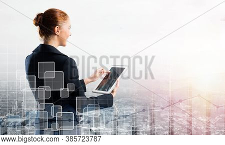 Young Businesswoman Using Tablet Computer. Double Exposure Concept With Modern Cityscape And Beautif