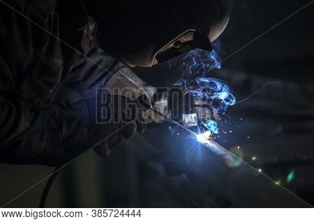 Welder At Work. Man In A Protective Mask. The Welder Makes Seams On The Metal. Sparks And Smoke When