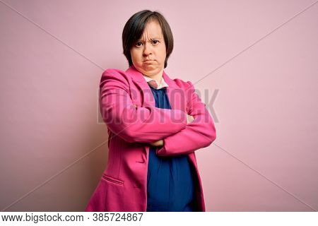 Young down syndrome business woman over pink background skeptic and nervous, disapproving expression on face with crossed arms. Negative person.