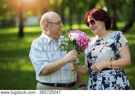 Happy Elderly Couple With Flowers. Handsome Man And Woman Senior Citizens. Husband And Wife Of Old A