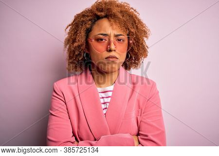 Young African American afro woman with curly hair wearing funny hearts sunglasses skeptic and nervous, disapproving expression on face with crossed arms. Negative person.