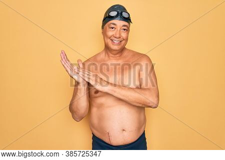 Middle age senior grey-haired swimmer man wearing swimsuit, cap and goggles clapping and applauding happy and joyful, smiling proud hands together
