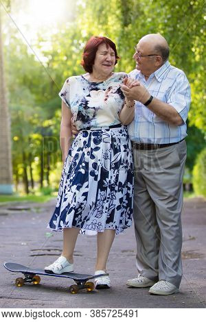 Happy Elderly Couple With A Skateboard. Handsome Man And Woman Senior Citizens. Husband And Wife Of