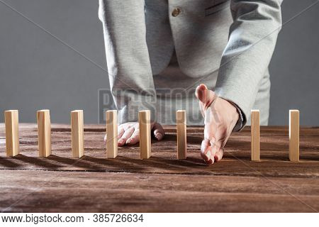 Businesswoman Interrupting Domino Effect By Stop Falling Wooden Dominoes. Operative Business Solutio