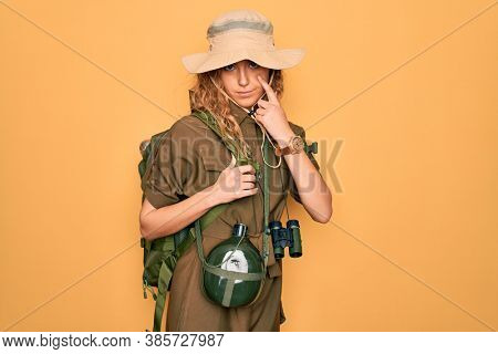 Young blonde explorer woman with blue eyes hiking wearing backpack and water canteen Pointing to the eye watching you gesture, suspicious expression
