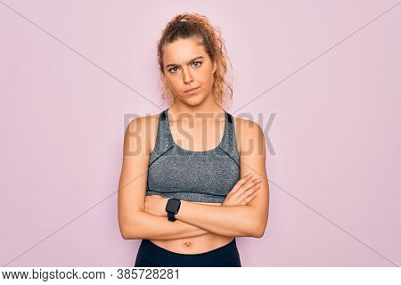 Young beautiful blonde sportswoman with blue eyes doing exercise wearing sportswear skeptic and nervous, disapproving expression on face with crossed arms. Negative person.