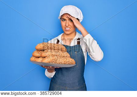 Young beautiful blonde baker woman with blue eyes holding tray with wholemeal bread cereal stressed with hand on head, shocked with shame and surprise face, angry and frustrated. Fear and upset