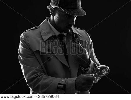 Old Fashioned Detective With Magnifying Glass Smoking Pipe On Dark Background, Black And White Effec