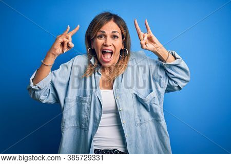 Middle age beautiful woman wearing casual shirt standing over isolated blue background shouting with crazy expression doing rock symbol with hands up. Music star. Heavy music concept.