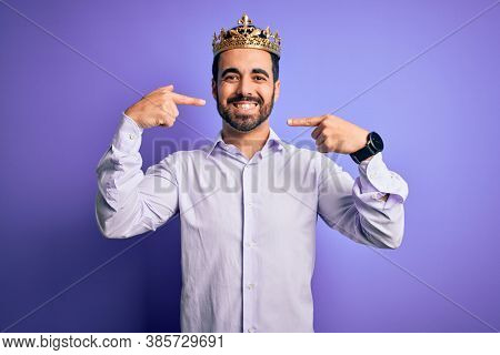 Young handsome man with beard wearing golden crown of king over purple background smiling cheerful showing and pointing with fingers teeth and mouth. Dental health concept.