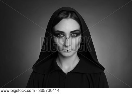 Mysterious Witch In Mantle With Hood On Dark Background. Black And White Effect