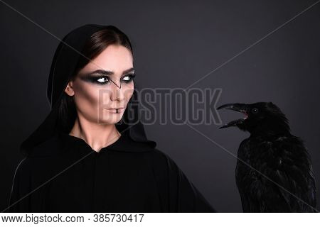 Mysterious Witch With Raven On Black Background