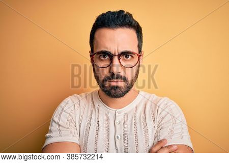 Young handsome man with beard wearing casual t-shirt and glasses over yellow background skeptic and nervous, disapproving expression on face with crossed arms. Negative person.
